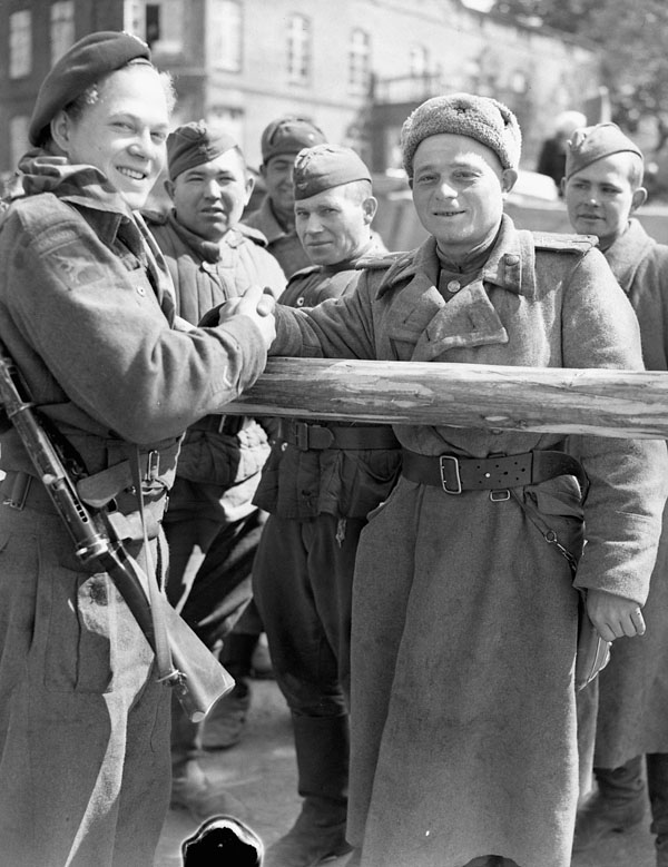 Unidentified Forward Observation Officer of the Royal Canadian Artillery (R.C.A.) shaking hands with a Russian soldier, Wismar, Germany, 4 May 1945.