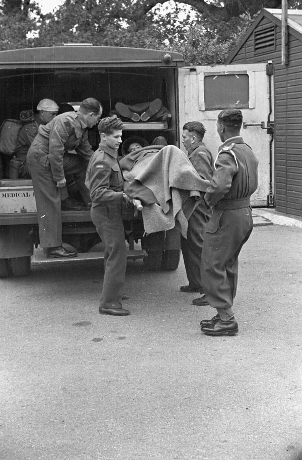 Personnel of a Casualty Clearing Station of the Royal Canadian Army Medical Corps (R.C.A.M.C.) evacuating