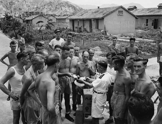 Lieutenant-Commander Fred Day and officers of the auxiliary anti-aircraft ship H.M.C.S. PRINCE ROBERT with liberated Canadian prisoners-of-war at Shamshuipo Camp, Hong Kong, August 1945.