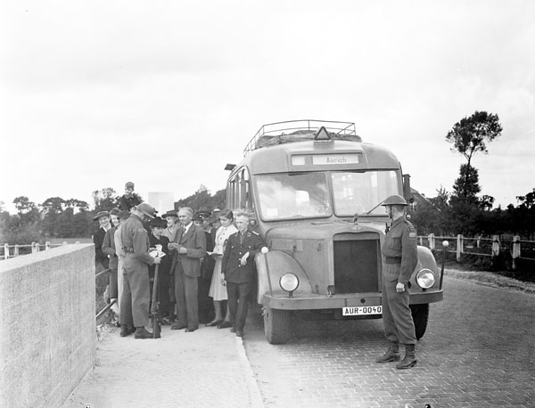 Riflemen Gordon Campbell and Jack Strickland of the Canadian Army Occupation Force (C.A.O.F.) checking the identity passes of bus passengers, Aurich, Germany, ca.26-27 August 1945.