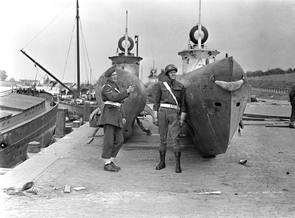 Lance-Corporals J. Lang and P.C. Ajas of No.1 Provost Company, Canadian Provost Corps (C.P.C.), guarding German submarines, IJmuiden, Netherlands, 25 May 1945.