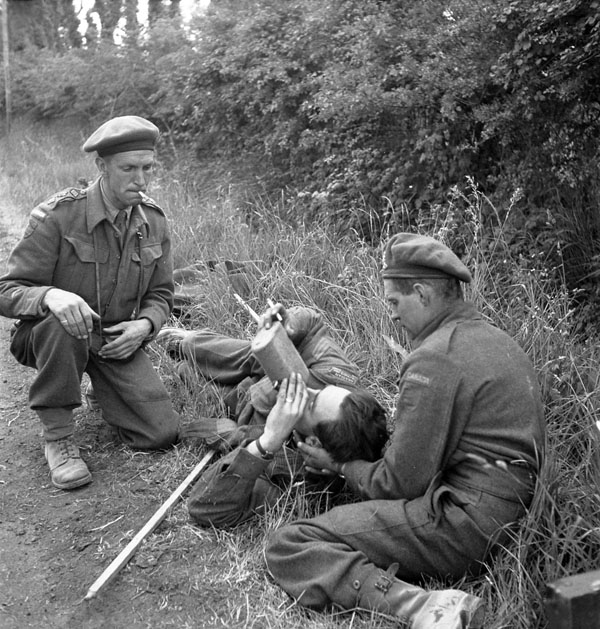 Sergeant W.G. Grant, who has broken his leg, receives assistance from Captain Colin McDougall (left) and Private M.W. Treganza, all of the Canadian Army Film and Photo Unit, Bayeux, France, 14 June 1944.