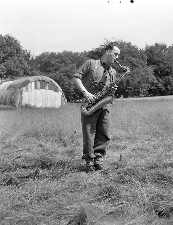Saxophonist Private Gordon Murray of the Canadian Army Show practicing in a field outside the Show's production centre, Guildford, England, 21 June 1945.