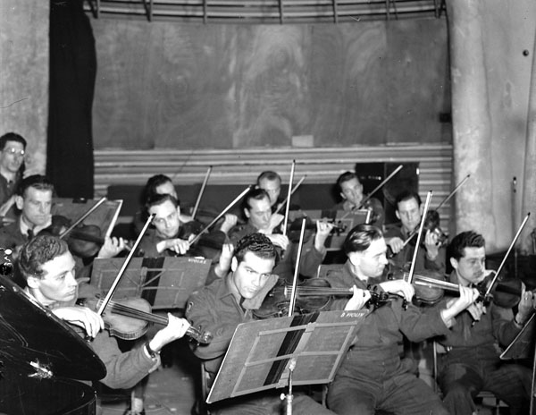 The string section of the orchestra during the Canadian Army Show Broadcast, London, England, 29 June 1945.