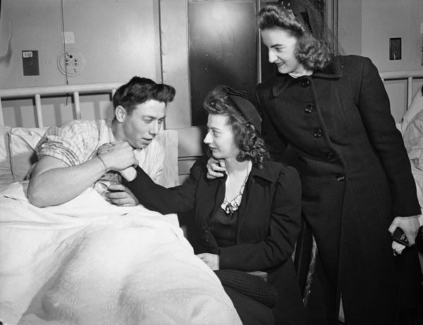 Unidentified survivor of the minesweeper H.M.C.S. ESQUIMALT, which was torpedoed by the German submarine U-190 on 16 April 1945, receives visitors at the Royal Canadian Naval Hospital, Halifax, Nova Scotia, Canada, April 1945.