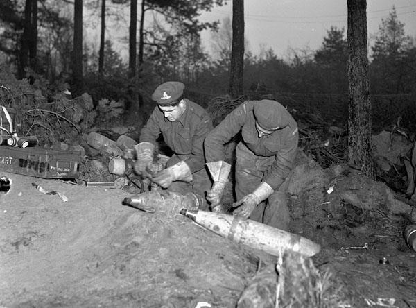Gunners T. Parenteau and A.J. Landry of a medium regiment of the Royal Canadian Artillery (R.C.A.) fusing 5.5-inch shells near Nijmegen, Netherlands, 8 February 1945.