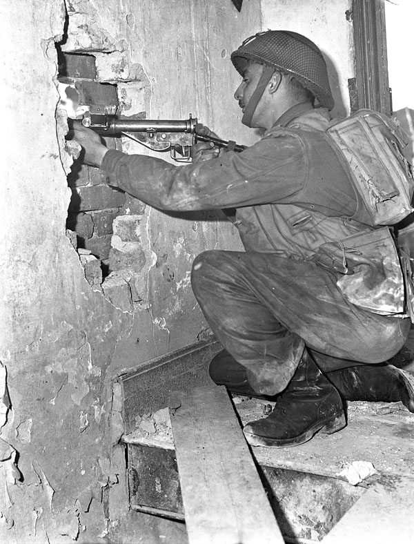 Captain Andy Mouflier of The Royal Winnipeg Rifles looking through a hole in the wall of a shattered building during a training exercise, England, 22 April 1944.