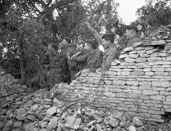 Personnel of an unidentified British Commando regiment waving to members of a Russian military delegation visiting the Normandy bridgehead, France, 28 July 1944.