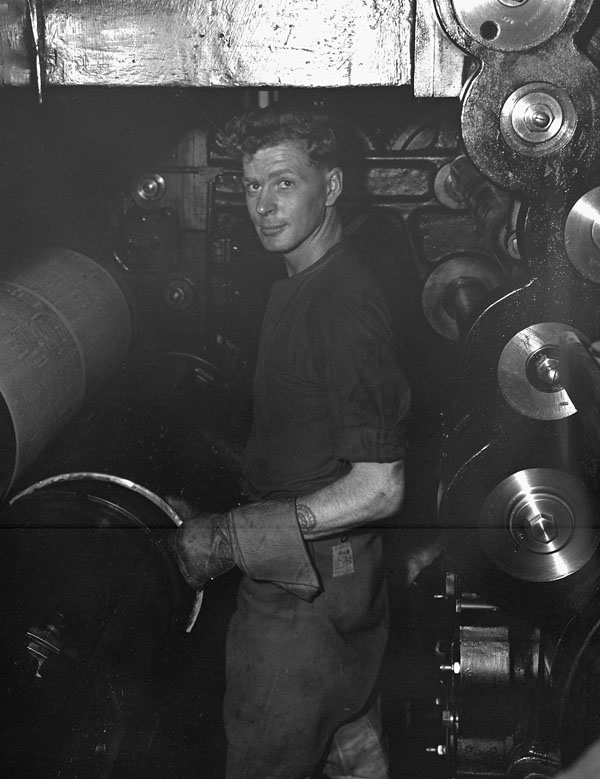 Private Tom Hunter putting a plate on the press during the printing of the first issue of the Maple Leaf newspaper, Caen, France, 28 July 1944.