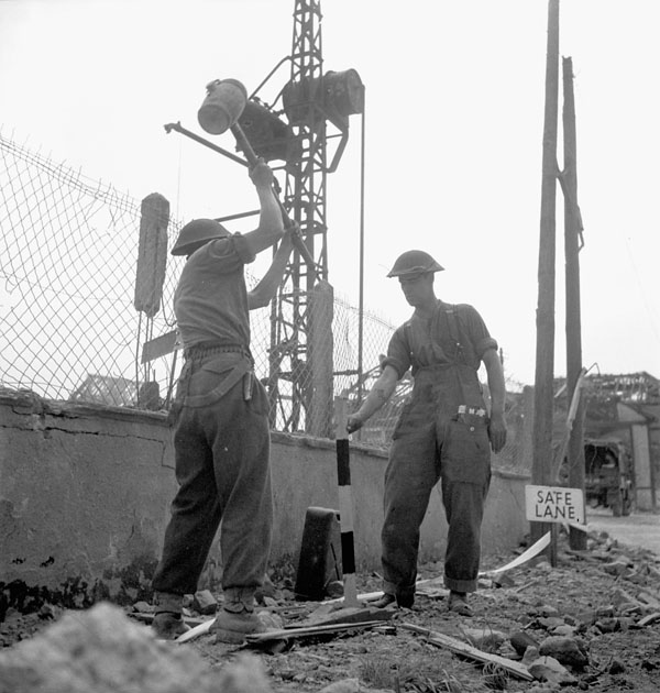 Sapper J.B. Sweeney and Lance-Corporal C.K. Halmsley of the Royal Canadian Engineers (R.C.E.)  pounding in safety stakes along a road in Vaucelles, France, 23 July 1944.