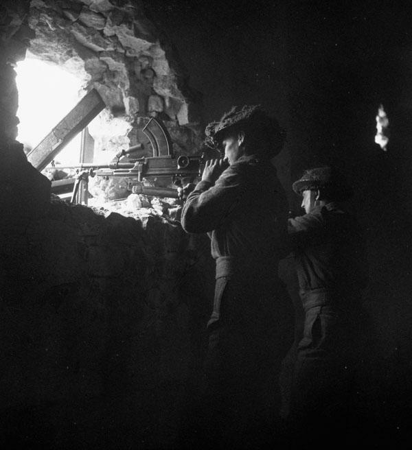An unidentified infantryman of the Regina Rifles Regiment manning a Bren gun position, Vaucelles, France, 23 July 1944.