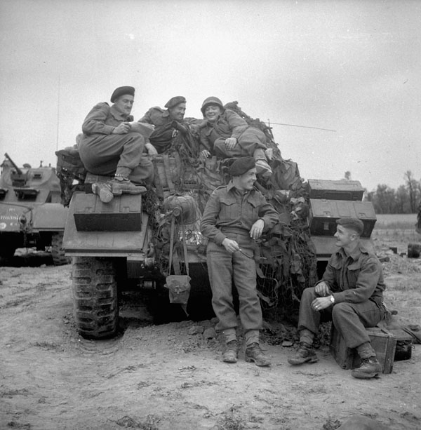 Troopers of the 12th Manitoba Dragoons with a Sherman tank of a Canadian armoured regiment near Caen, France, 19 July 1944.