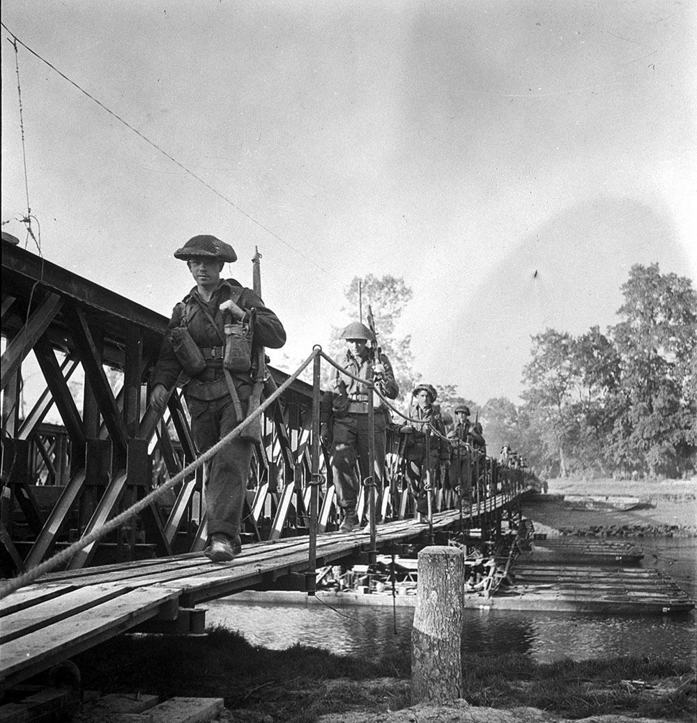Infantrymen of the Stormont, Dundas and Glengarry Highlanders crossing the Orne River on a Bailey bridge built by the Royal Canadian Engineers (R.C.E.) en route to Caen, France, 18 July 1944.