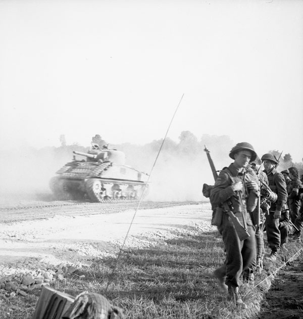 Infantrymen of the 8th Canadian Infantry Brigade  passing a Sherman tank while advancing to attack the industrial area of Caen. Ranville, France, 18 July 1944.