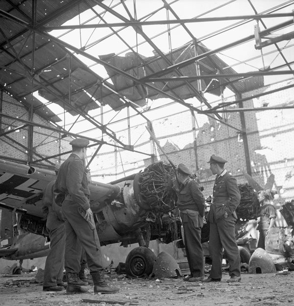 Unidentified Canadian officers examining a damaged Henschel Hs 129 aircraft of the Luftwaffe, Carpiquet, France, 12 July 1944.