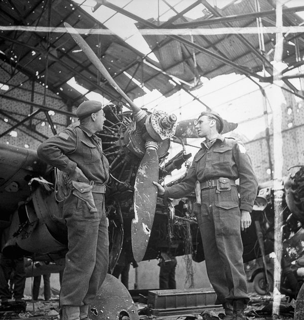 Captain J.W. Ferguson and Lieutenant D.L. Almas examining a damaged Henschel Hs 129 aircraft of the Luftwaffe, Carpiquet, France, 12 July 1944.