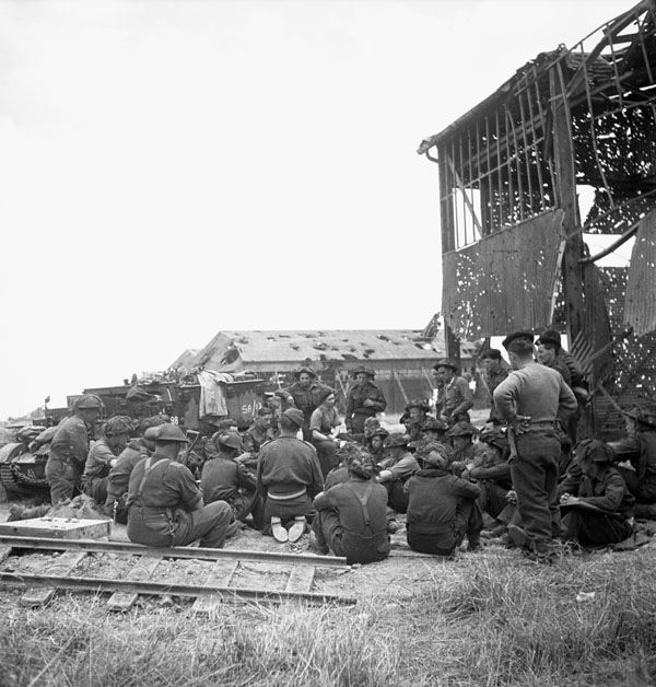 Briefing of Canadian infantrymen outside a hangar at the airfield, Carpiquet, France, 12 July 1944.