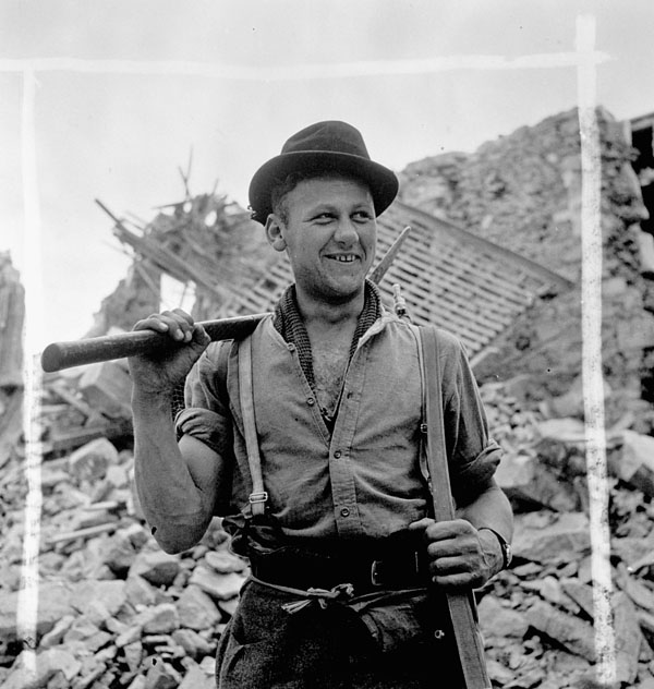 Private H. Koebe of the 9th Canadian Infantry Brigade helping to clear rubble, Carpiquet, France, 12 July 1944.