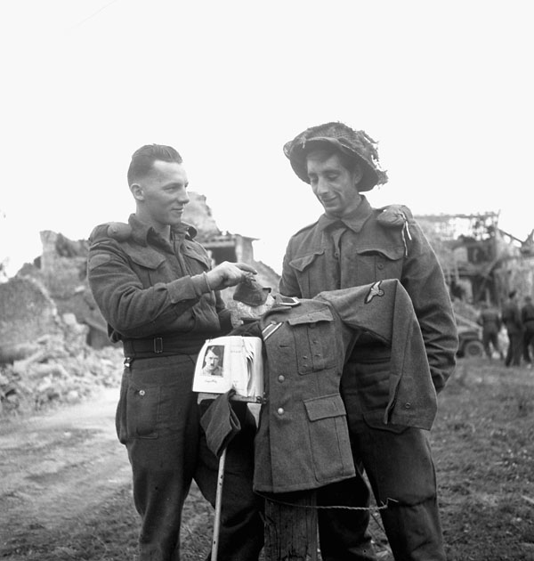 Privates Bob Miller and Randall Willis of the 7th Canadian Infantry Brigade with their own scarecrow, which wears a German uniform, Authie, France, 9 July 1944.