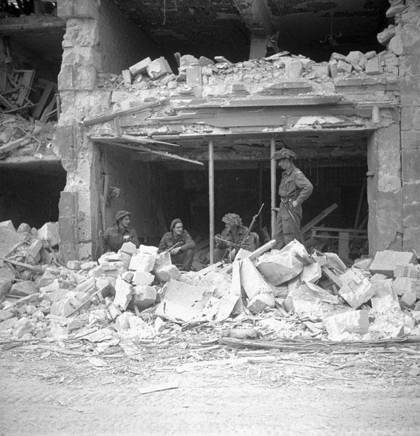 Infantrymen of The Regina Rifle Regiment inside a damaged building, Caen, France, 10 July 1944.