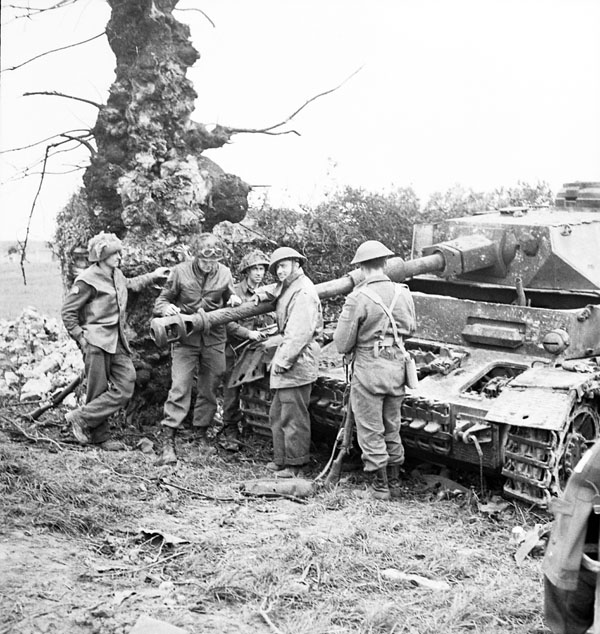 Canadian infantrymen examining a disabled German PzKpfW IV tank, Gruchy, France, 9 July 1944.