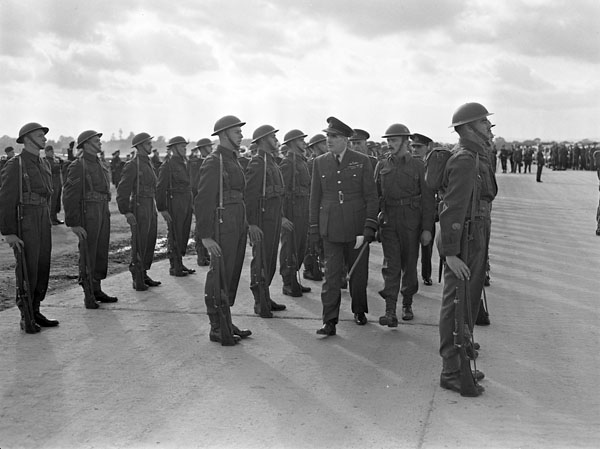 Air Chief Marshal Sir Christopher L. Courtney of the Royal Air Force inspecting a Canadian guard of honour at the official opening of the airfield which was constructed by the Royal Canadian Engineers at Dunsfold, England, 16 October 1942.