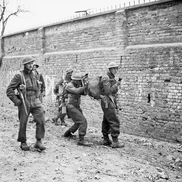 Infantrymen of The Loyal Edmonton Regiment using a walkie-talkie radio during an advance, Ortona, Italy, 21 December 1943.