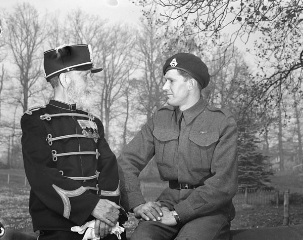 Trooper L.W. Goss of the 8th Princess Louise's Hussars (New Brunswick) talking with a retired Dutch soldier as they sit on an old cannon which bombarded Algiers in 1816. Arnhem, Netherlands, 16 April 1945.