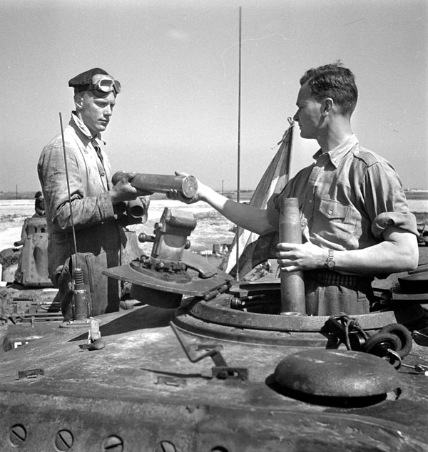 Unidentified troopers of Lord Strathcona's Horse (Royal Canadians) loading shells into their tank during a training exercise, England, 20 April 1943.