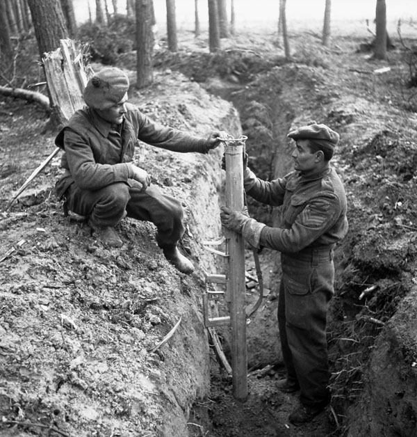 Private R. Neel and Sergeant R.B. Swain of The Queen's Own Cameron Highlanders of Canada examining a German bazooka anti-tank weapon found in an abandoned trench in Hochwald, Germany, 5 March 1945.