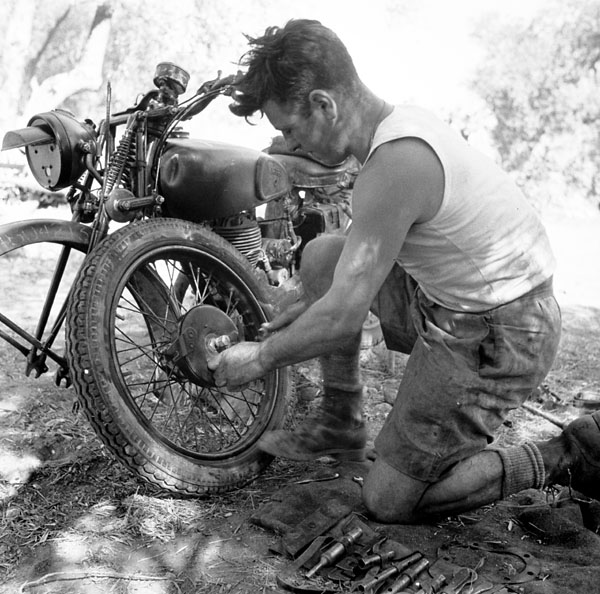 Private F. Jones of The Royal Canadian Regiment repairing his motorcycle near Militello, Italy, 18 August 1943.