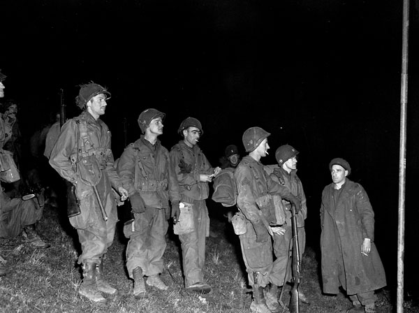 Paratroopers of the 101st Airborne Division, U.S. Army, waiting to board storm boats operated by the 23rd Field Company, Royal Canadian Engineers (R.C.E.), near Nijmegen, Netherlands, 27 November 1944.