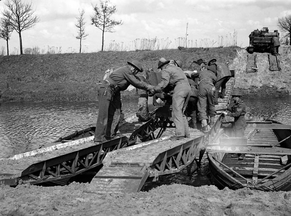 Gunners of the Royal Canadian Artillery pushing a six-pounder anti-tank gun across a canal, Netherlands, 7 April 1945.