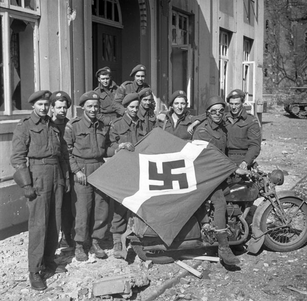 Personnel of The Lake Superior Regiment (Motor) with a captured German flag, Friesoythe, Germany, 16 April 1945.