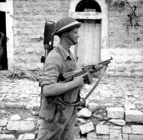 Corporal E.H. Pruner of The Hastings and Prince Edward Regiment, who carries both a PIAT anti-tank weapon and a Thompson sub-machine gun, Motta, Italy, 2 October 1943.