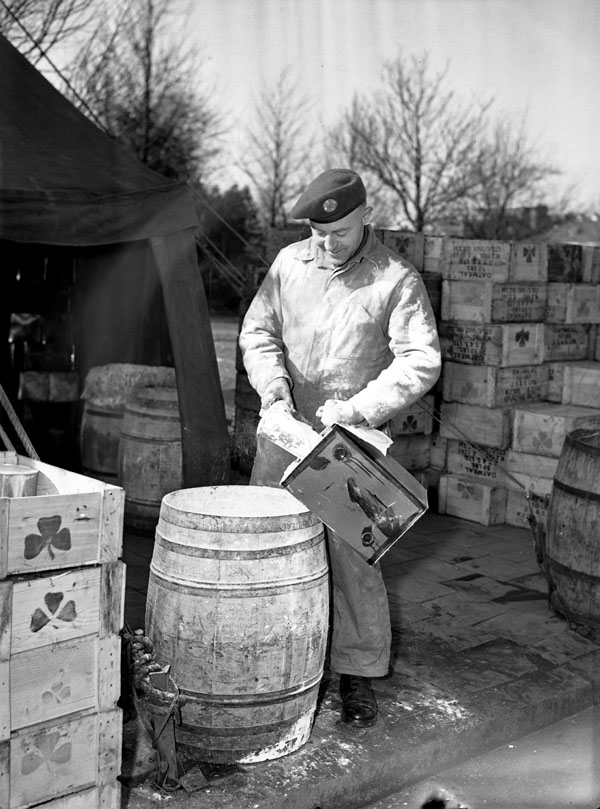 Private Hugh Dryden of No.35 Canadian Army Troops Composite Company, Royal Canadian Army Service Corps (R.C.A.S.C.), preparing a drum of powdered milk, Nijmegen, Netherlands, 14 February 1945.