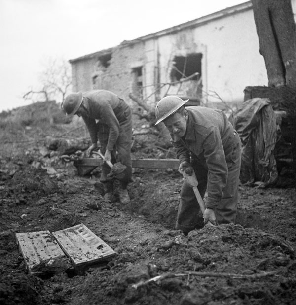 Privates J. Miller and W.H. Hall, both of The 48th Highlanders of Canada, digging a slit trench during a pause in a German counter-attack, San Leonardo di Ortona, Italy, 10 December 1943.