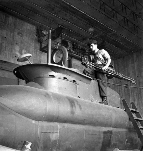 Sergeant A.H. Calder of the Canadian Army Film and Photo Unit, who carries a camera and tripod, examining one of the German miniature two-man submarines discovered in a shipyard at Kiel, Germany, 18 May 1945.