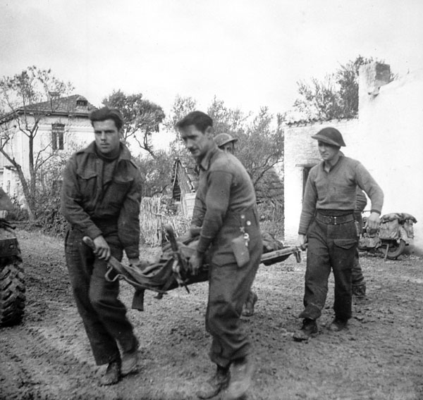Infantrymen of The Seaforth Highlanders of Canada carrying a comrade who was killed by shellfire while escorting German prisoners, San Leonardo di Ortona, Italy, 10 December 1943.