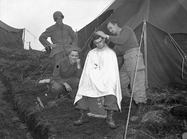 An unidentified infantryman of Le Régiment de Hull getting a haircut, Kiska, Aleutian Islands, August 1943.