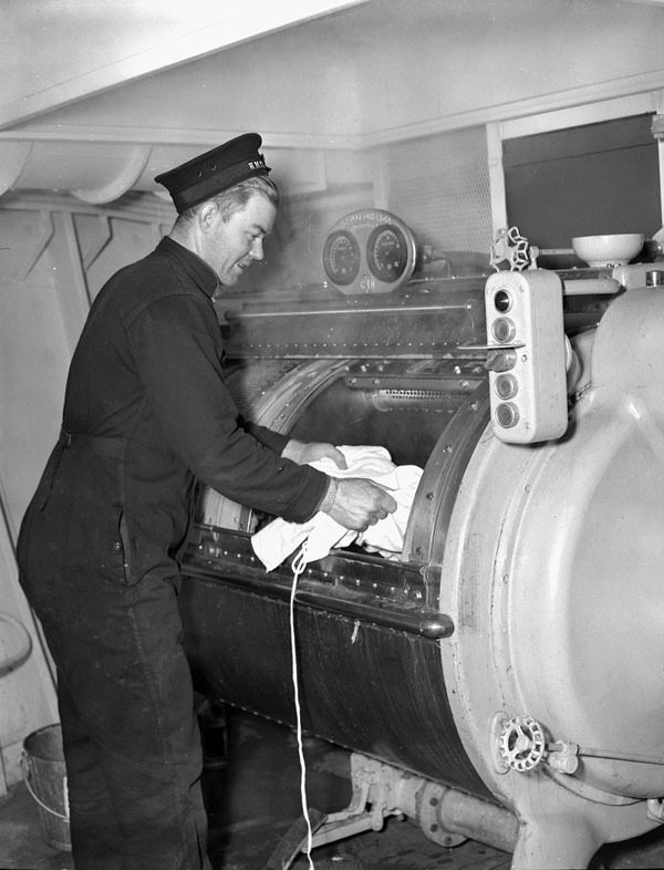 Stoker First Class L.H. Swallow in the laundry compartment of H.M.S. NABOB, Vancouver, British Columbia, Canada, January 1944.