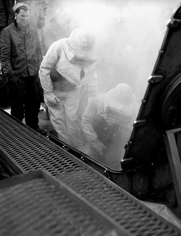 Canadian firefighters from H.M.S. NABOB fighting a fire in a simulated boiler room at a U.S. Navy firefighting and damage control school, Manchester, Washington, United States, January 1944.