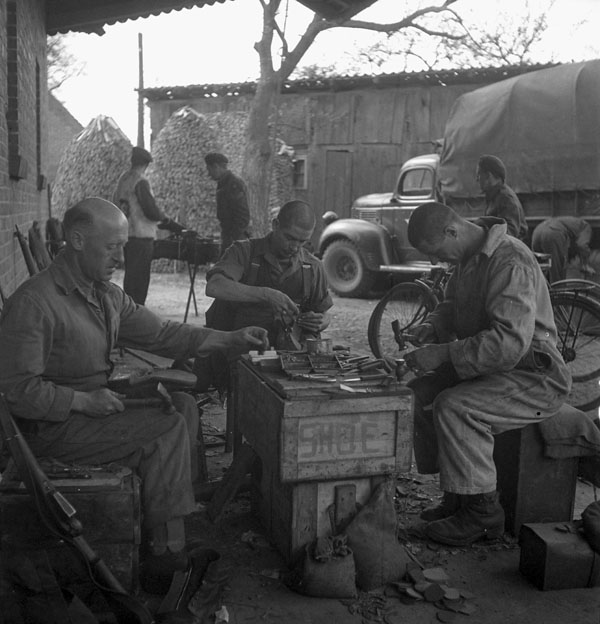 Personnel of the 1st Canadian Parachute Battalion repairing boots, Brelingen, Germany, 14 April 1945.
