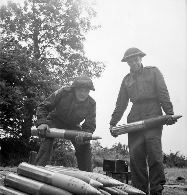 Gunners J.R. Robinson and L.T. Groves, both of 34 Battery, 14th Field Regiment, Royal Canadian Artillery (R.C.A.), stacking 105mm. shells in Normandy, France, 20 June 1944.