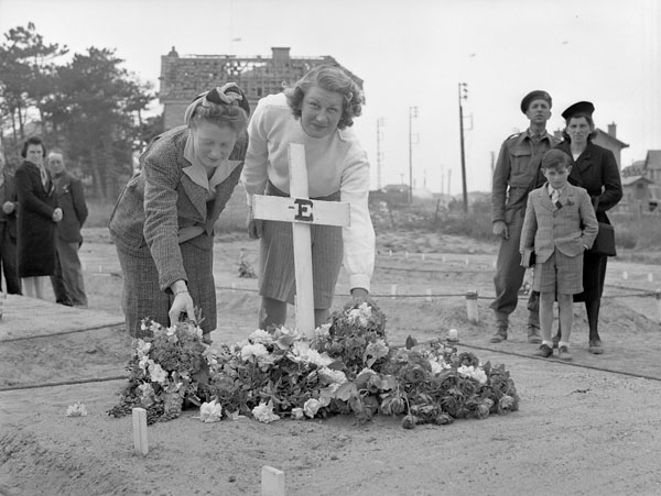 Two French women placing flowers on the grave of a Canadian soldier, Bernières-sur-Mer, France, 18 June 1944.