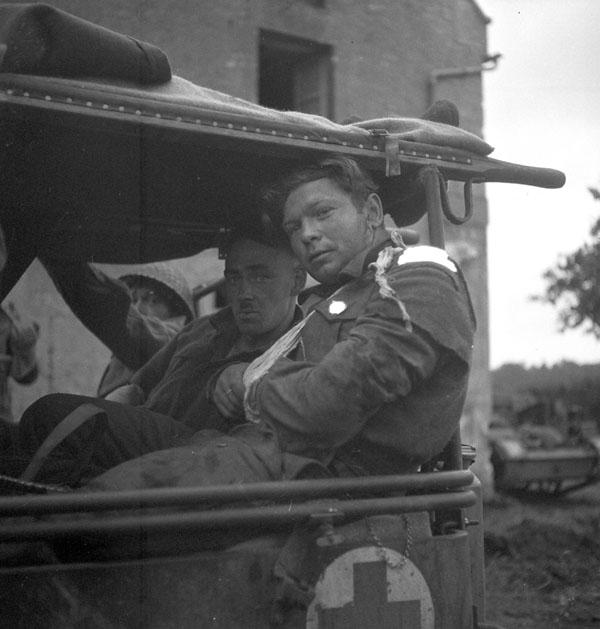 Wounded infantrymen of Le Régiment de la Chaudière near Carpiquet, France, 4 July 1944.