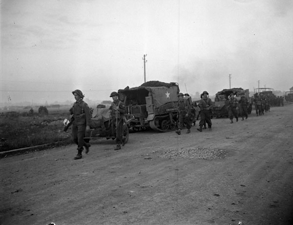 Infantrymen of an unidentified Canadian regiment advancing past a Universal Carrier, which is towing an anti-tank gun, during Operation TOTALIZE south of Vaucelles, France, 25 July 1944.