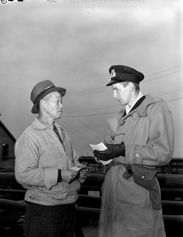 An unidentified officer of the Royal Canadian Naval Volunteer Reserve (R.C.N.V.R.) examining the papers of an unidentified Japanese-Canadian fisherman, Steveston, British Columbia, Canada, 10 December 1941.