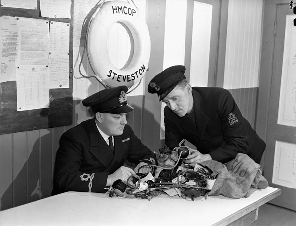 An unidentified Lieutenant of the Royal Canadian Navy Volunteer Reserve (R.C.N.V.R.) and a Petty Officer of the Royal Canadian Navy examining engine parts removed from expropriated Japanese-Canadian fishing boats, Naval Control Observation Post, Steveston, British Columbia, Canada, 10 December 1941.