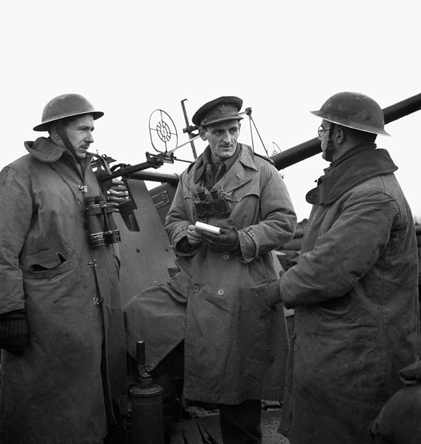 War correspondent Douglas Amaron of the Canadian Press interviewing two British members of a Bofors anti-aircraft gun crew, Grave, Netherlands, 11 February 1945.